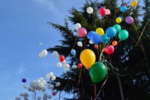 Decine di palloncini colorati si stagliano nel cielo azzurro di Varese